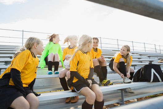 Soccer players sitting on bleachers