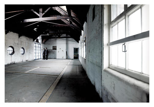 Businessmen Visualizing Empty Warehouse As Office Space