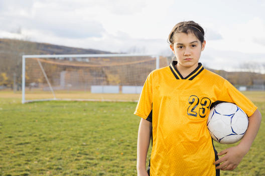 Portrait of confident soccer player on field