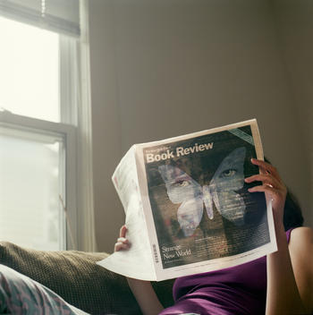 A young woman reads a newspaper, hiding her face.