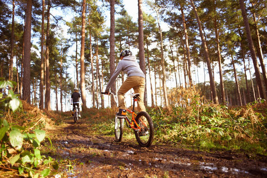 Twin brothers racing BMX bikes in muddy forest