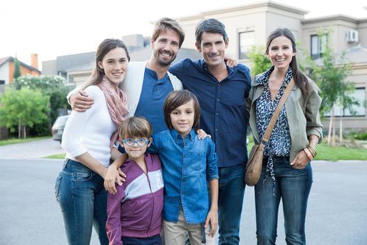 Family posing together on suburban street, portrait