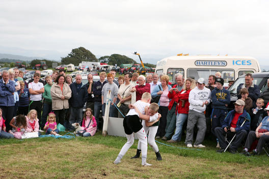 Crowds gather at Gosforth Agricultural Show to watch two boys compete in a Cumberland and Westmorland wrestling match. The boys are dressed in traditional Cumberland wrestling costumes.