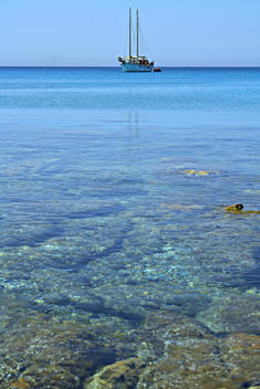 The crystalline water of the Sardinian sea, with a boat in the distance.