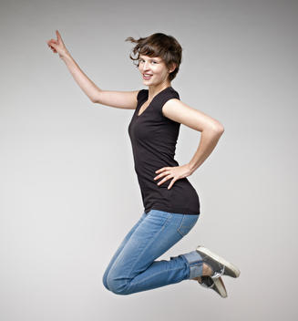Portrait of young woman jumping, smiling
