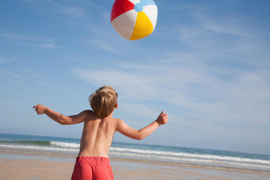 A boy in swimming trunks on the beach, with a large beach ball in the air above him.