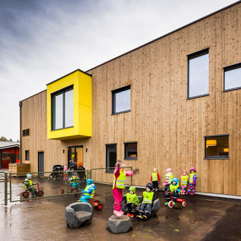 Children playing in the rain outside of a nursery school designed by Link Arkitektur, Stockholm, Sweden.
