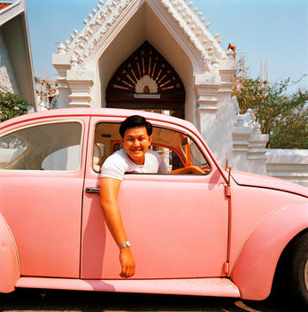 Smiling Man Leaning Out Of Pink Vw Bug