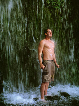 Young man standing in falls, shirt off, laughing