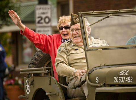 Grandfather and Grandmother in Memorial Day parade reacting to their grandchildren