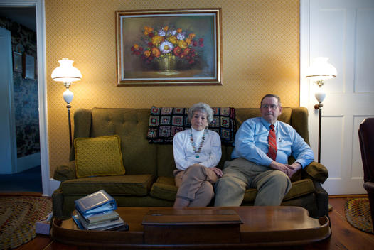Senior Couple Relaxing On A Sofa In Their Living Room