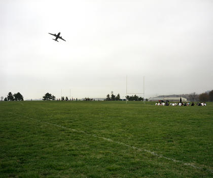 Airplane taking off over people playing sport on a field, Washington DC, USA.