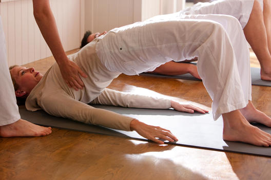 Yoga instructor helping woman during a yoga practice