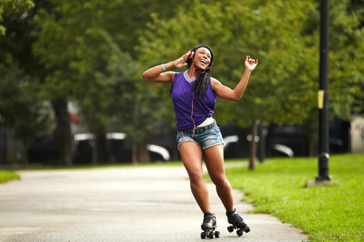 Young Woman Roller-Skating And Listening To Music