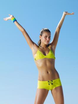 Young Woman In Bikini Arms Raised On The Beach