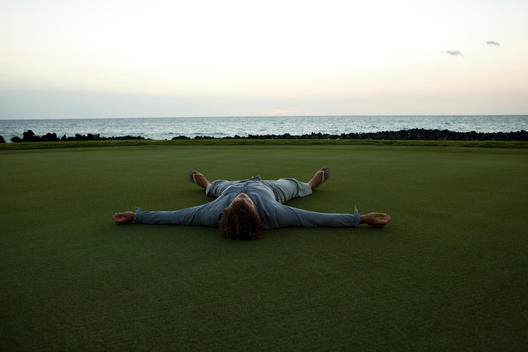 Man Lying On Golf Course In Hawaii