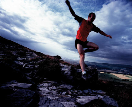 Man Jumping Over Rocks During A Cross Country Run.
