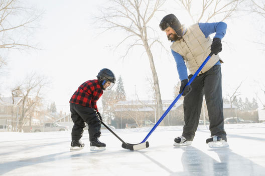 Father and son playing ice hockey