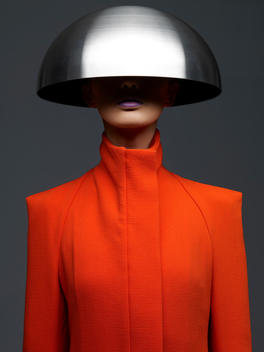 Woman In Futuristic Fashion Outfit Of Orange Coat With A Bowl On Her Head