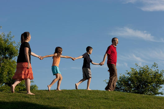 Family Walks Hand In Hand Through The Museum Campus In Chicago.