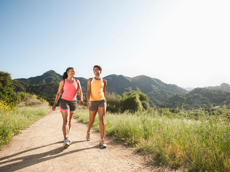 Athletic women walking together on remote trail