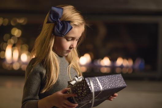 Non-specific holiday portrait of a young girl seated in front of a modern lit fireplace in which holiday lights are reflected on the glass. She is holding a gift and trying to determine what might be inside.