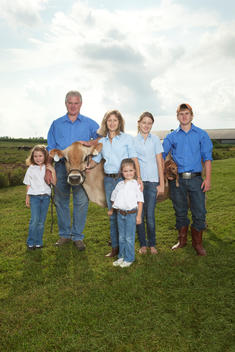 Family Posing With A Cow