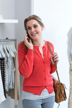 Young woman on mobile phone in fashion shop