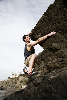 An athletic man rock climbing at the beach