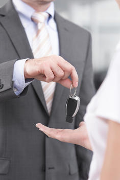 At the car dealer, Salesman handing over car key to client