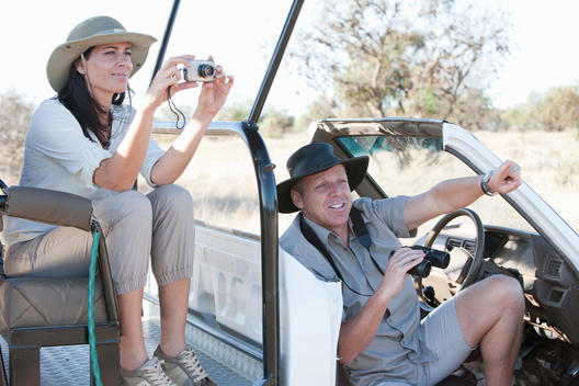 Couple on safari in off road vehicle, Stellenbosch, South Africa