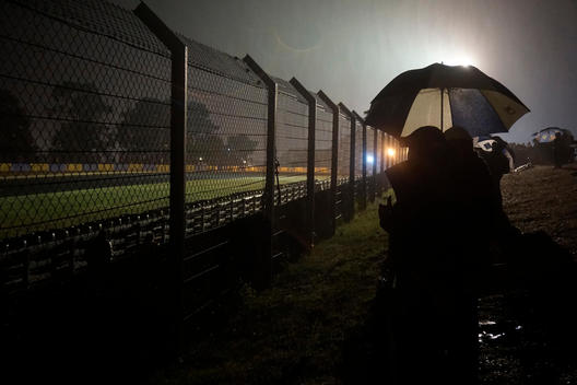 People stood in rain with umbrellas, at motorsport event