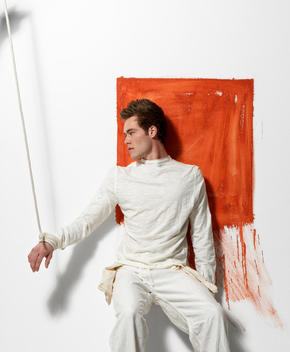 Young Man Leaning On Wall With Orange Square And Hand Tied To Rope