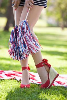 Caucasian woman in heels holding pom-poms