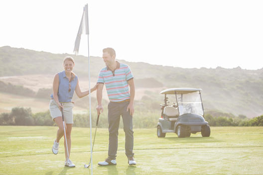 Couple playing golf on course