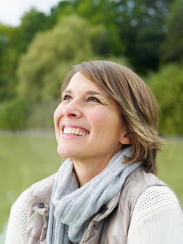 Germany, Munich, Mature woman in warm clothing near lake, smiling