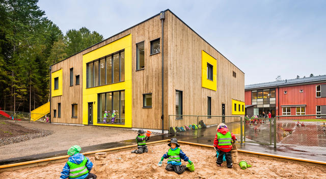 Children playing in a sand pit in the rain outside of a nursery school designed by Link Arkitektur, Stockholm, Sweden.