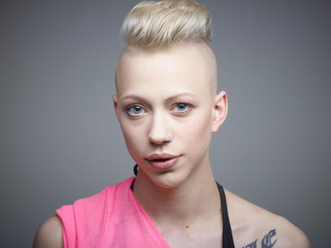 Portrait of young woman with tattoos against grey background, smiling