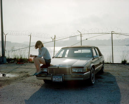 Woman Sitting On Hood Of The Car