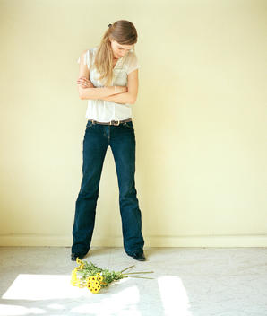 Frustrated Woman Standing Above Discarded Bouquet Of Flowers At Her Feet