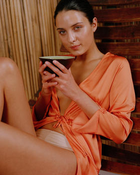 woman relaxing and drinking tea in spa