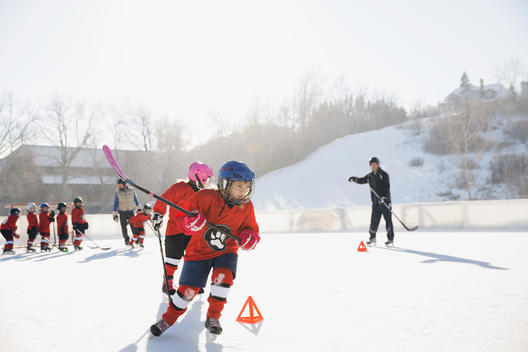 Ice hockey players training on outdoor skating rink