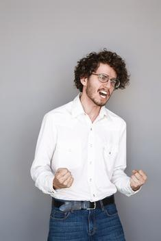 A portrait of a well dressed brunette man with glasses yelling in a studio setting.
