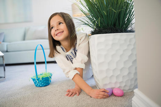 Cute girl collecting plastic Easter eggs at home