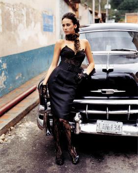 Fashionable woman posing on a vintage car.