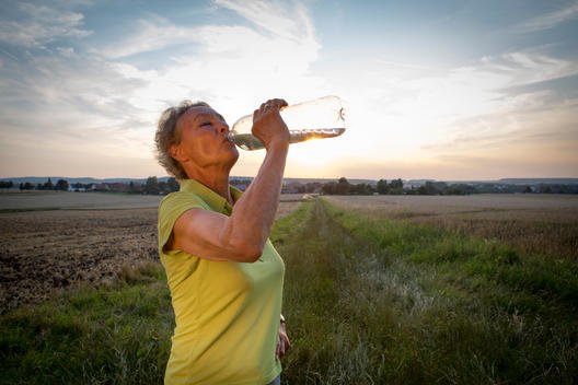 Portrait of senior woman drinking out of water bottle