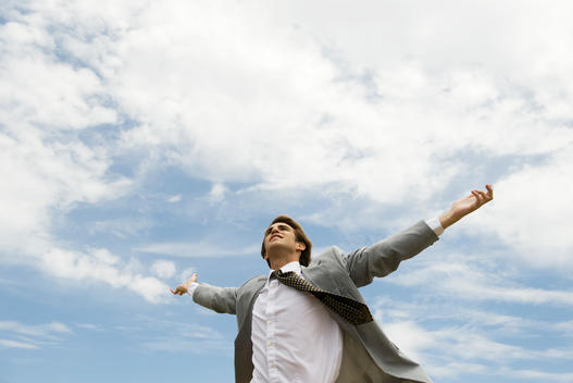Businessman with arms outstretched against cloudy sky