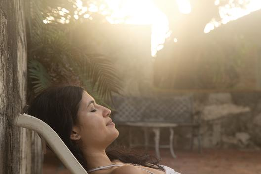 A beautiful young, brunette woman relaxes poolside on holiday as the sun shines in the background, Havana, Cuba.
