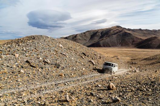 Bus driving through rocky desert landscape