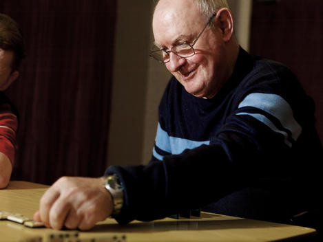 Senior Man Playing Dominoes At Retirement Home